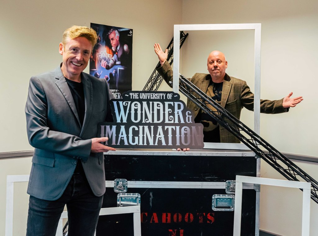 "Two men standing beside a flight case marked Cahoots NI, surrounded by frames and lighting bars. The man in the foreground holds a sign saying ""The University of Wonder and Imagination."""